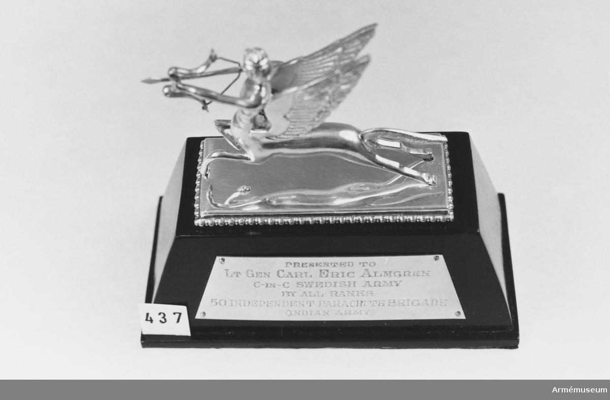 """Samhörande nr är 294-299, 321-350, 400-448 (437-438). Minnestecken från 50. fallskärmsbrigaden, Agra, Indien. Emblem i silver på trä från indiska fallskärmsbrigaden i Agra. Överlämnat 1975-01-24 under CA besök vid indiska armén jan 1975 """"Pesented to Lt. Gen. Carl Eric Almgren, C-in-C Swedish Army, by all ranks 50 Independent Parachute Brigade, Indian Army."""" Svartmålad, hög träsockel med silverplatta, graverad med: """"Presented to..."""". Däröver en kentaur med människohuvud. I armarna pil och båge. Mått, bottenplattan: 130x65 mm, total höjd: 120 mm."""