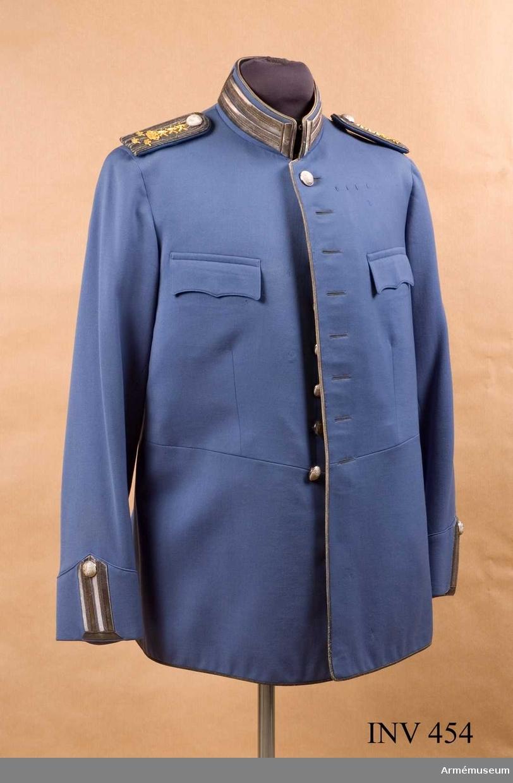 """Stl F 52. Uniformsplansch för kavalleriet, Åke Dahlbäck. För ryttmästare. Ljusblå kamgarnssatin med silvergalon och metallknappar Avskuren i midjan, framtill åtta st knappar och knapphål. Silvergalon runt hela ytterkanten. Två st bröstfickor med lock. Locken fodrade med satin i uniformens färg. Ficköppningen skodd med satin. Fickpåse av grått fodertyg. Krage 60 mm hög med ett """"knapphål"""" av silvergalon. Hophäktas upp- och nedtill med hyska och hake. Under dessa skyddsbit i svart satin. Tre st häktor för fastsättning av vit stärkt krage. På axlarna band av tygets färg för fastsättning av axelklaffen, tre på var axel. På vänster bröst fyra st sydda tränsar för ordensbandsspänne. Bak skörtet en ficka i sömmen med en snedställd stolpe, galonkantad. Två st knappar i midjan och en på var fickstolpe nedtill. Hopsytt sprund mitt bak, galonkantat. Innerficka vänster bröstsida. Spänntampar i fodertyget med knäppspänne mitt fram. Ärmen fodrad med vit bomullssatin, avslutas nedtill med ett spetsigt uppslag, försett med """"knapphål"""" i silvergalon på höjden. Upptill knapp. Knapp m/1845."""