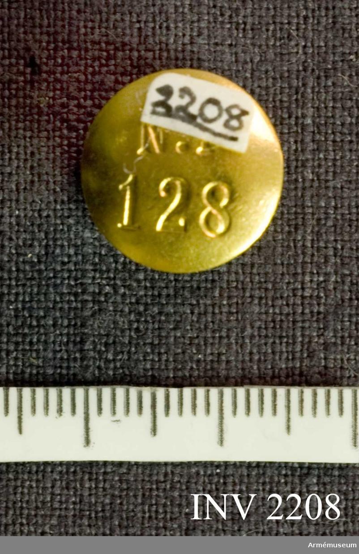"""Av guld och blå emalj med verkets emblem i guld. Platt hals  fäst vid en något större platta (större än knappen, d 15 mm)  märkt """"128"""". Bärs i slagets knapphål.Styresman O Cederlöf har i egenskap av f d flygare fått bära  denna knapp."""
