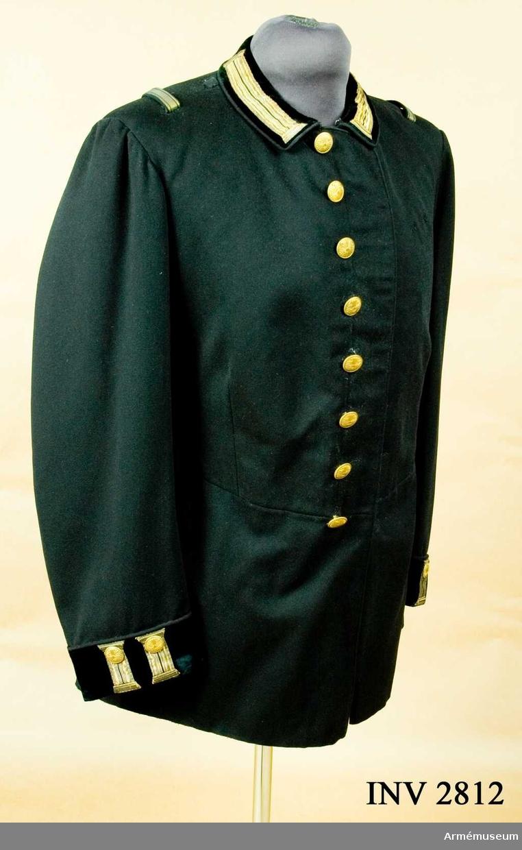 """Stl B 48. Av mörkblå, närmast svart kläde med mörkblå passpoal runt kragen, framkanter, ärmuppslag och ficklock. Fällkrage av mörkblå sammet med """"knapphål"""" i guldgalon. Enkelknäppt med åtta knappar av kårens m/1886 ä. Ärmuppslag av mörkblå sammet med stående """"knapphål"""" av guldgalon. Figursydd, avskuren i midjan och har ett sprund mitt bak, något omlottgående. Vid dettas sida, dolt i ett veck, finns en ficka med fasonerat ficklock och tre knappar, varav en placerad i midjan, en mitt på fickan och en nedtill. Svart foder, i livet matélasserat. En innerficka på vänster sida. Spänntamp i livet. Hake saknas i livet. Har tillh. givarens far, major J F Cornell, som blev löjtnant i kåren 1864, kapten 1878 och majors avsked 1903. Han var bl.a. stiftare av Ostkustbanan. Källa: Svenska Teknologföreningen."""