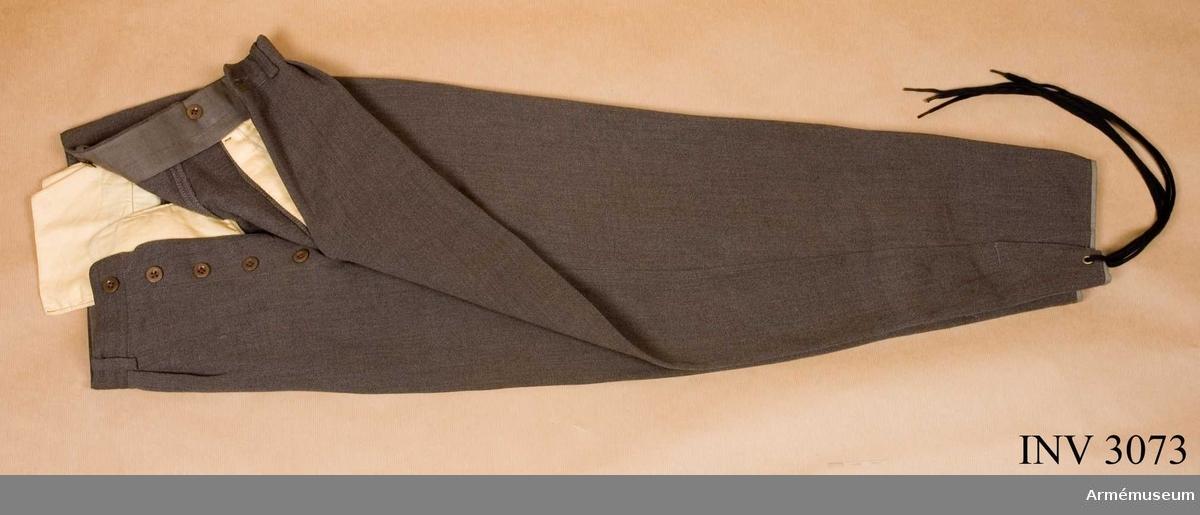 Stl 50. Av gråbrungrön ylleadiagonalväv. Förefaller vara ett uppblandat material, cellull? Linning med hällor för livrem och knappar för hängsle. Julpknäppta. Fickor i sidsömmarna och en bakficka på höger sida. Benen är något avsmalnande mot foten. Ett sprund på utsidan av smalbenet som hålles ihop med ett svart kängsnöre, vilket är draget genom ett öljetterat hål.