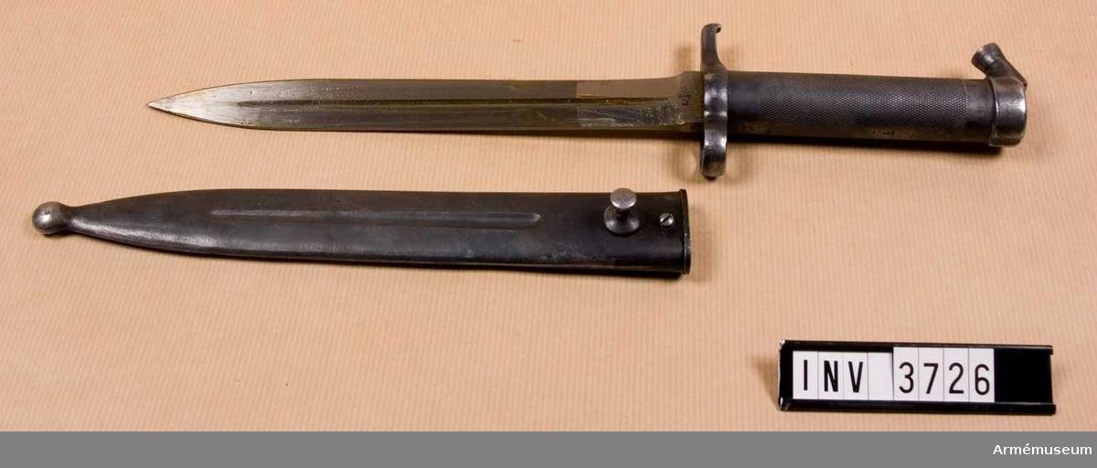 Knivbajonett m/1896 t gevär m/1896, m/1938/automatgevär m/1942.Består av: 1 bajonett, 1 balja av stål.Helt tillv. av stål med rörformigt lättrat grepp med konisk låsknapp och pipring. Rak, eneggad klinga med smal blodskåra på båda sidor. Klingb vid fästet: 25 mm. Pipringens id: 15,5 mm. Balja, l: 232 mm, vikt: 120 gr.