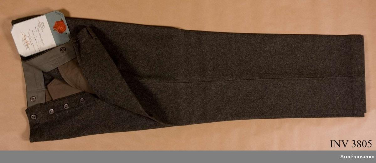 """Av gråbrungrön kommiss. Utan uppslag. Midjebandets insida fodrad  m bomullstwills och har sex hängsleknappar av bly. Sex hällor f  bälte. Två snedställda sidfickor. P g a rådande förhållanden  ersattes blyknappar m i handeln förekommande material. Vidhängande etikett anger dag f fastställande: """"4.april 1941"""". Undertecknat av Per Edvin Sköld, chef FÖD och Henry Kellgren chef LKE."""