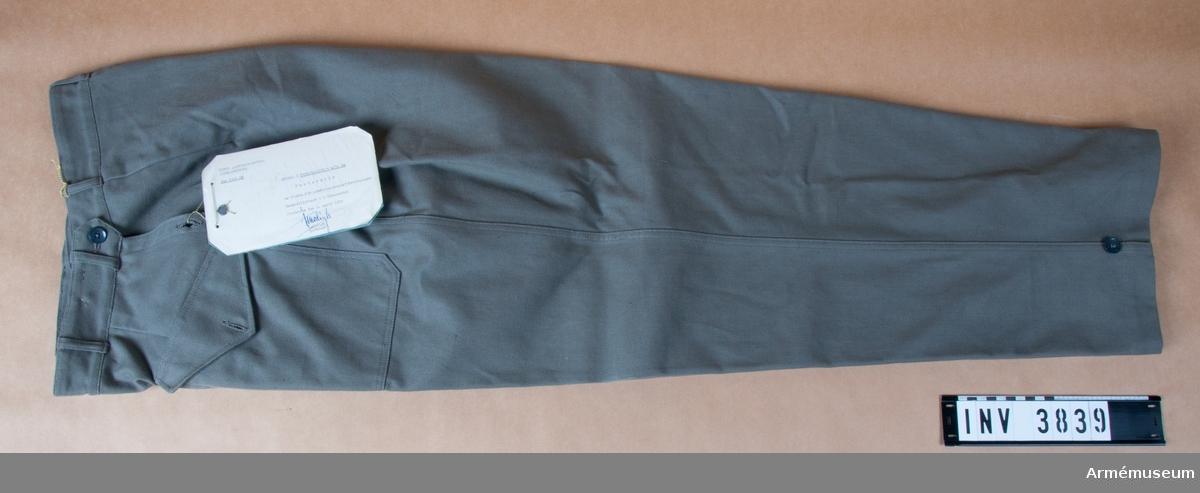 """Av gråbrungrön bomullstwills. På framstycket två halvt snedställda, påstickade fickor med spetsskurna lock knäppta m en knapp. I en högra fickan en mindre innerficka. I vardera sidan ett ca 150 mm långt sprund med en knapp mitt på. Midjebandets framsida avslutas som en slejf m knapphål. I var sida två knappar för att reglera midjevidden. Nedtill i var yttersöm, en knapp och i innersöm en slejf med knapphål för minskning av benvidden. I fram-/bakstycke två insydda veck. Sju hällor för bälte. Vidhängande etikett: """"Fastställd av Chefen för arméintendenturförvaltningen, Generallöjtnant C.A. Ehrensvärd den 2.april 1955, I. Modigh, Byråchef""""."""