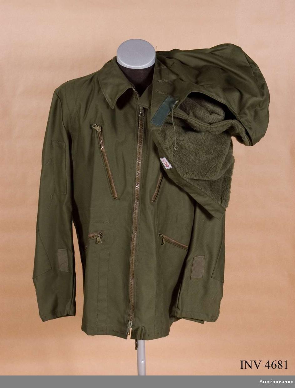 Storlek C 50. Jackan är tillverkad av olivgrön varpsatin, 50 % polyester och 50 % bomull. Denna fältjacka samt till den  hörande fältbyxor m/1969 flyg tilldelas arméns och marinens flygande personal, således ej personal vid flygvapnet. Den är  högknäppt i halsen medelst blixtlås i framkanten. Den är försedd med två insydda, snedställda bröstfickor, två insydda snedställda sidfickor samtliga med blixtlås, grenslejf fodrad  med twills fastsydd vid ryggens nederkant. Har räddningssele av  syntetband fastsydd på jackans insida med början vid grenslejfens ytterände och omsluter även ärmhålen. Selen är  åtkomlig genom en i ryggen blixtlåsförsedd öppning med lock.  Midjetunnel med dragsnöre för reglering av midjevidden. På  höger överärm ficka för ficklampa, på vänster tyredelad ficka  för pennor. Ärmen är nedtill försedd med en c:a 10 cm lång slits, en knapp på insidan samt två knapphål för reglering av ärmvidden. Fästband av bomull för kartklämmor placerade på  bägge ärmarna c:a 12 cm från nederkanten och c:a 4 cm från  framstycket intill bröstfickans överkant. Halvt ryggfoder av bomullstwills. Fickfoder av samma material. Vid jackans nederkant dels en knappslejf för dold knäppning, dels en tunnel  vid varje sidsöm för genomträdning av resårband som knäpps på  knappar för reglering av stussvidden. Nedanför halshålssömmen  är en knapphålskant fastsydd fodrad med twills försedd med fyra  knapphål och fem knappar för fastknäppning av tillhörande huva. Märkning: På ryggens insida under hängaren finns vävd storleksetikett C 50, till höger därom stämpel: Tre kronor 76  HAGA (firmanamn för tillverkaren AB HAGA-PRODUKTER, Örebro).