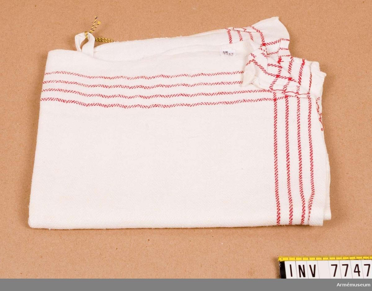 Handduk.Vit med fyra röda parallella linjer längs två kanter. Märkt med tre kronor.Ingår i fotomaterielsats 7 låda 1.