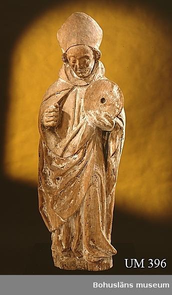Träskulptur, troligen föreställande biskop Quirinus.  Skulpturen har tillhört ett numera försvunnet medeltida altarskåp av nordtysk karaktär, daterad till 1500-talets början och som suttit i Skredsviks gamla kyrka.  Fiender till biskop Quirinus band en kvarnsten om hans hals och försökte dränka honom. Men han flöt, trots stenen, ett Guds tecken. Skulpturen har också ansetts föreställa S:t Halvard. Datering och tillverkningsort attribuerad i samtal 2006 med professor Jan Svanberg, Uppsala. Se avbildning på fotografi UMFA54467:0009, den mellersta skulpturen. Från gamla, rivna kyrkan i Skredsvik. Skulpturen bör ha tagits ur bruk då kyrkan revs någon gång efter 1852 och då placerats på vinden med övrigt äldre kyrkligt material som inte ansågs passa i den nybyggda kyrkan. Nya kyrkan byggdes 1855-1856. Delar av gamla kyrkans sten återanvändes i den nya. Ett utförligt syneprotokoll från 1851 beskriver Skredsviks gamla kyrka.   Ur handskrivna katalogen 1957-1958: S:t Halvard, Skredsvik H.89 cm; helgonet håller en kvarnsten i höger hand, attributet i vänster förlorat; färgen flagn. maskäten.  Gustaf Brusewitz noterar skulpturen i början av 1860-talet i samband med resor i Bohuslän, dels som utsänd för KVHAAA och inför nytrycket av Holmbergs Bohusläns Historia och Beskrifning 1864.  Utdrag af Protokoll, hållet med Skredsviks församling i dess kyrkas Sakristia 1861 d. 7de oktober. P1. Med anledning af skrifelse från Rektor J. Rodhe I Uddewalla, hwilken skrifvelse nu upplästets, upfordra- des församlingens utlåtande huruwida densamma vill till Museum i bemäldte stad aflåta den härvarande gamla dopfunten samt 3ne Katholska bilder, som saknar wård. Utlåtandet blef af plurabiliteten nekande, ehuru en och annan medgaf det som för alla borde wara obestridligt, att dessa reliker från gamla Kyrkan för ifrågavarande ändamål bättre användes. Upplästs och vidkäntds, som ofwan        Joh. Persson(?) Rasmus Nilsson i Bro, Tobias Hansson i Böll Nils Hermansson i Stensbacka tingets riktighet