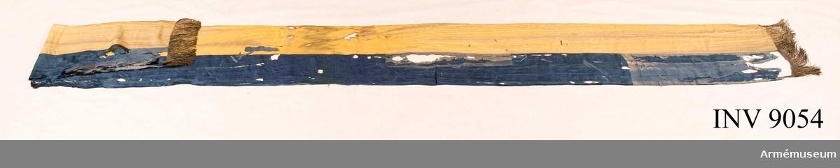 Kravatten, hälften blå och hälften gul på längden, i sidentyg. Den har en enkel frans i guld.  Samhörande nr är 9053-9055.