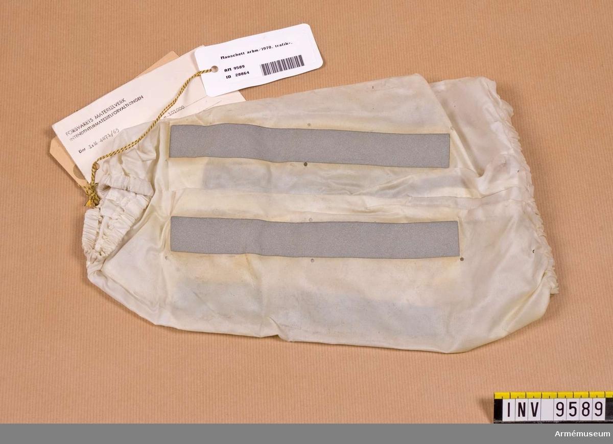 Av vitt nylontyg med remsor av fluorescerande band  (självlysande). Resår upptill och nedtill. Lufthål. Gåva från FMV.
