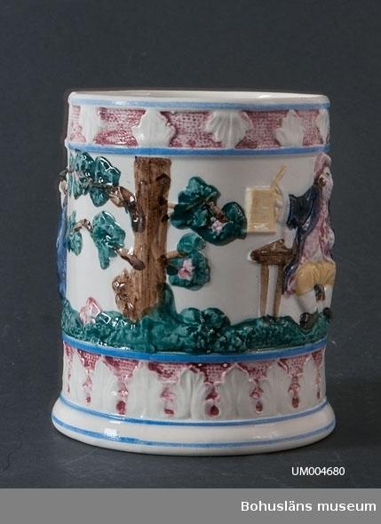 Troligen tillverkad i England. Svagt uppåt avsmalnande kärl med hänkel. Vit med polykrom dekor i relief. Motivet visar två män, den ena med en mugg i handen och den andra med ett krus, samt träd. I över- och underkant är det en bård med blad. Även hänkeln har dekor i relief med blad och vindruvsklasar. Föremålet har sprickor och lagningar samt en bit som fattas vid mynningskanten.  Ölost (eller ölsupa, ölsoppa) är en traditionell bohuslänsk dryck som bygger på svagdricka och mjölk som kokas och vispas. Recept se UM005098  Muggen hörde till den typ av souvenir som bohuslänskt sjöfolk gärna köpte med sig från främmande länder.  Ur handskrivna katalogen 1957-1958: Porslinsmugg. (ölostmugg). Mynningsdiam.: 11,7 H: 15. Vitt porslin med figurer i färg. Sönder. Sprucken och lagad  Lappkatalog: 62