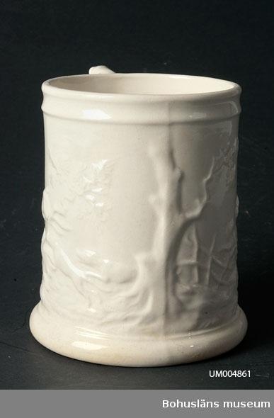 """Svagt uppåt avsmalnande kärl med en hänkel. Vit med dekor i relief. Motivet visar en jaktscen - en jägare till häst som jagar en hjort. På hänkelns ovansida ligger en hund. Under botten är det intryckt: """"GUSTAVSBERG"""" samt en trea (3) och """"VI"""". Föremålet är krackelerat.  Ölost (eller ölsupa, ölsoppa) är en traditionell bohuslänsk dryck som bygger på svagdricka och mjölk som kokas och vispas. Recept se UM005098.  Ur handskrivna katalogen 1957-1958: Ölsupemugg, brunvit Mynningsdiam.: 11,8 H: 15,5. Porslin. Jaktmotiv. En spricka, eljest hel.  Lappkatalog: 62"""