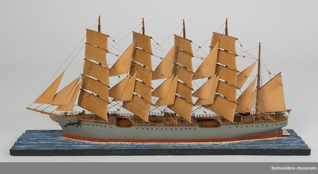 """594 Landskap BOHUSLÄN 503 Kön MAN 394 Landskap BOHUSLÄN  Skepp (bark), """"FRANCE"""" från Rouen, med fem master och gråmålat skrov. I aktern är det en fransk flagga. Skeppet är monterat på en rektangulär träplatta.  Ur handskrivna katalogen 1957-1958: Barken """"France"""" Kölens L. 71. Modell på platta. Föremålet helt. Från kapten Olssons saml., Fiskebäckski  Ur Bohusläningen 1947-11-08: """"Den femmastade barken """"France"""" är det senaste tillskottet till museet och det fartyg som syns på bilden. """"France"""" var en fransk båt, som på sin tid var världens största segelfartyg. Den hade en längd av ca 124 meter, bredden var 16 m. och djupgåendet 8 m. """"France"""" hade en segelyta av 6,650 kvm. och lastade 7.500 ton. Besättningen uppgick till 55 man. Denna båt har på ett minutiöst vis återgivits i modellen, som har kostat kapten Olsson ej mindre än 2.000 arbetstimmar.  För ytterligare information om förvärvet, se UM5087."""