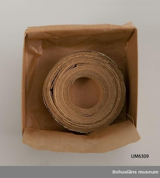 Ur handskrivna katalogen 1957-1958: Kristidsljus Impregnerad pappersremsa tillverkad i Uddevalla. Rullens D 7.6 cm remsans bredd 1.8 cm.  Hel. Gåva Rosa Jacobowskys sterbhus.  Rosa Jacobowsky (1860-1954), gift med grosshandlare Efraim Jacobowsky (1851-1929), Uddevalla.  Lappkatalog: 90