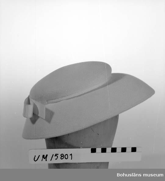 471 Tillverkningstid 1955 CA Vit, låg kulle, brett något klockat brätte. Vitt ripsband runt kullen med rosett baktill. Buren till kappa UM 15797. Se UM 15792.