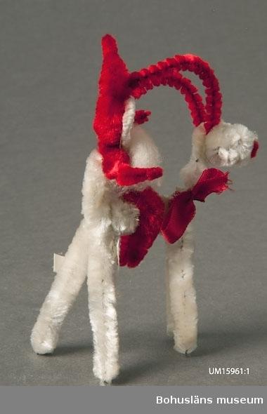 Tomte av röda piprensare, ridande på bock av vita och röda piprensare.  Se UM015810