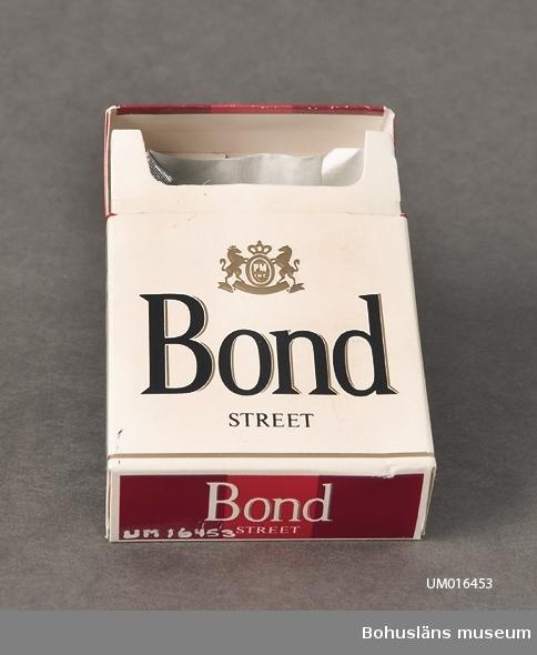 """Tom cigarettförpackning av märket """"Bond"""". Vitt, svart och rött tryck. Varningstext på ena sidan: Kärlsjukdomar. Vid kärlsjukdomar är det viktigt att sluta röka. Socialstyrelsen."""