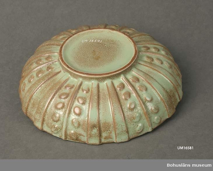 Fruktfat.  Grönt med bruna inslag, geometrisk relief på utsidan. Fotringens diameter 10.5 cm.