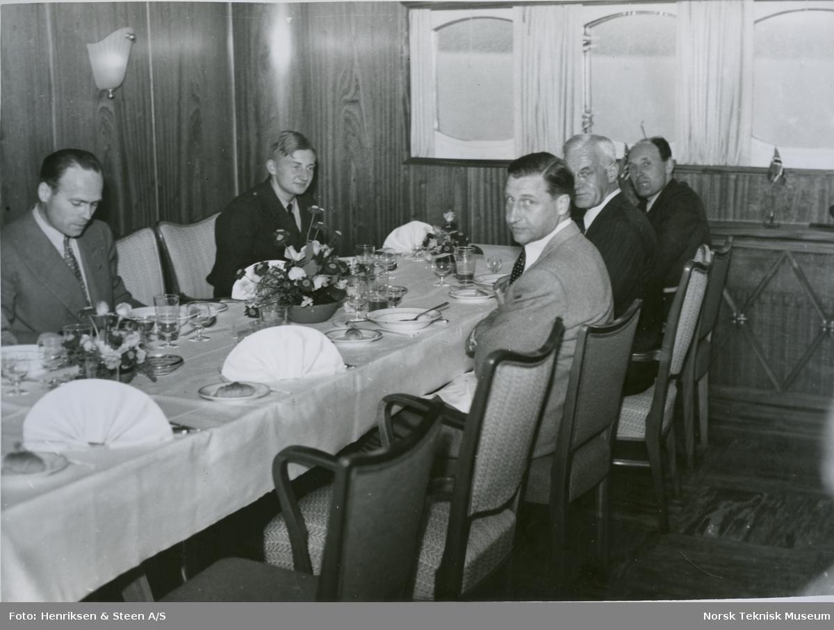 Menn rundt bordet på cargolineren M/S Heina, B/N 488 under prøvetur i Oslofjorden 15. juni 1950. Skipet ble levert av Akers Mek. Verksted i 1950 til J. L. Mowinckels rederi.