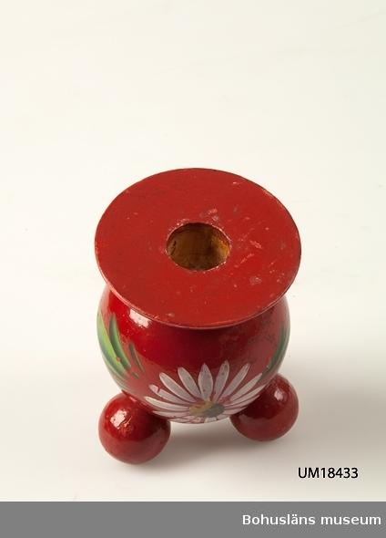 Kulljusstake på tre runda fötter. Rödmålad med målad prästkrage med gröna blad. För ljus med diameter 20 - 22 mm.