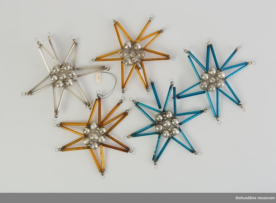 Glasstavar och kulor trädda på metalltråd så att de bildar en stjärnform. Se UM019325: Föremål från insamling av föremål från vindskontor över Antonssons Livs m.m., kvarter Ridhuset , Södra Drottninggatan 12, Uddevalla (rivningsfastighet).