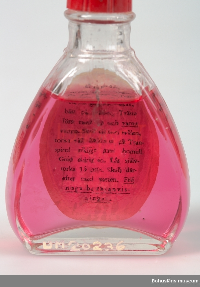 """Trekantig flaska med röd skruvkork av plastmaterial med flytande rosarött klart innehåll. Oval etikett med rosor och text: """"Amarant Transpirol mot transpiration AB Oxygenol Stockholm"""". På etikettens baksida bruksanvisning som kan läsas genom flaskan. """"Användes ett par gånger i veckan, bäst på kvällen. Tvätta först med tvål och varmt [understruket] vatten. Skölj väl bort tvålen, torka väl. Badda så på Transpirol rikligt med bomull. Gnid aldrig in. Låt självtorka i 15 min. Skölj därefter med vatten. Följ noga bruksanvisningen. [understruket]   Reklamfilmen Oxygenol Transpirol mot transpiration från 1955 är sökbar via Svensk mediedatabas (SMDB).  Se bilaga."""