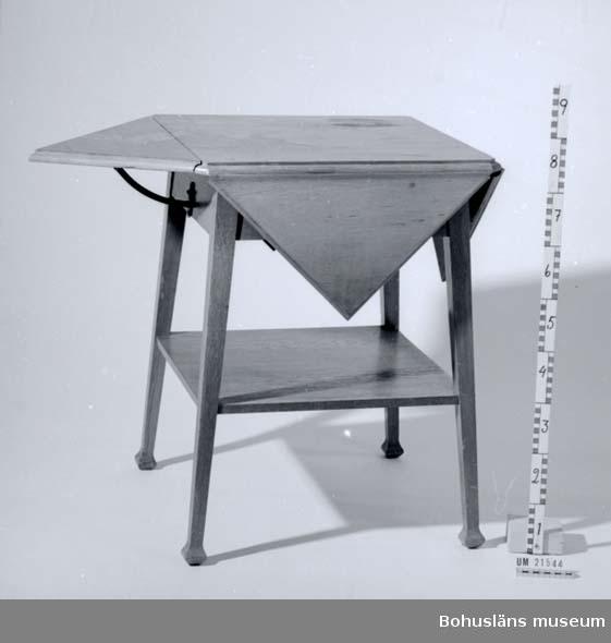 Fyrsidigt bord med fyra tresidiga klaffar. Hylla undertill. Ben lätt vinklade utåt.