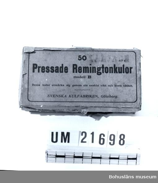 """594 Landskap BOHUSLÄN  Asken är klädd med rött papper. Märkt: """"Pressade Remington kulor, 50 modell B. Dessa kulor utmärka sig genom sin exakta vikt och stora lätthet. Svenska kulfabriken Göteborg"""".  UMFF 47:7."""