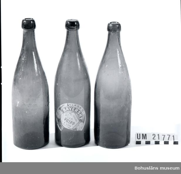"""594 Landskap BOHUSLÄN 394 Landskap VÄSTERGÖTLAND  Del av kork sitter kvar i en flaska, liksom etikett på samma flaska. Brunt glas med fattning för naturkork. Flaska nr 1  märkt: """"L 2/3 Lit. 1900. 16"""".  Flaska nr:2 märkt  L 2/3 Lit.1900.13.  Flaska nr:3 märkt  L* F.  UMFF 49:3.  Ölflaskan är Sveriges andra standardiserade bruksföremål, d v s ett föremål med i landet överenskomna mått oavsett tillverkare.  Sveriges första """"standard"""" är tändsticksasken.  Liandergårdens Glasmuseum drivs av Limmareds hembygdsförening och  glasbrukets historia presenteras på deras hemsida.  Följande uppgifter ur hemsida Collector-Sweden på Internet, 2009: """"Knoppölflaskan kom som den andra standardiserade produkten efter tändsticksasken i Sverige.  Knoppölflaskorna tillverkades under den tid de var munblåsta i den tredelade formen som  J.P Jönsson, Liljedals disponent, fick patenterad 1852. (Fogelberg, Nisbeth, Liljedals glasbruk, sid 162 f).  Den första flaskmaskinen inköptes av Hammar på hösten 1909.  (ABF Södra Närke, Glasfolket Buteljglasbruket i Hammar 1854-1930, sid 59).  Stora vinster kunde göras då flaskorna gjordes i ett moment utan att man behövde lägga på ringen """"knoppen"""" senare, som man fick göra vid munblåsning. De andra glasbruken följde efter några år i Hammars fotspår och installerade flaskmaskiner.  Arbetet mot en standard inom ölflaskorna kom att börja när den automatiska tappningsanordningar  introducerades. Den enhetliga flasktypen tillverkades av bryggeriägaren Anders Bjurholm samt korkfabrikören G.E BoÃ«thius. (Glasboken, Hermelin, Welander, Legenda, Borås 86, sid 278ff).  Flaskan skulle vara lätt att göra ren, den skulle kunna återanvändas och den skulle förslutas med naturkork. Arbetet med den nya typen av ölflaska baserades på metersystemet, som sedan 1869 kom att ligga tillgrund för allt varuutbyte.  (Kulturen, 1987, sid 89)  De första försöken med flaskan kom att göras i samarbete med Hammars glasbruk. Den första knoppölflaskan skall enligt uppgift från Svenska b"""