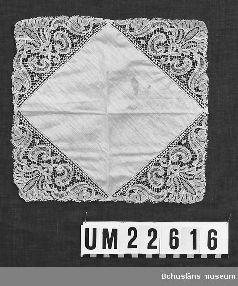 594 Landskap BOHUSLÄN  Vit. Näsduken har påsydd triangelformad spets längs sidorna.  UMFF 123:6
