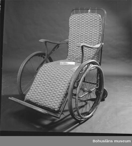 Stålstativ. Nosagbotten. Benstöd går att fälla upp och ryggstödet att fälla ned.  Gummihjul med yttre träringar för att driva stolen framåt.  Försedd med madrass med bomullsöverdrag. Träarmstöd.