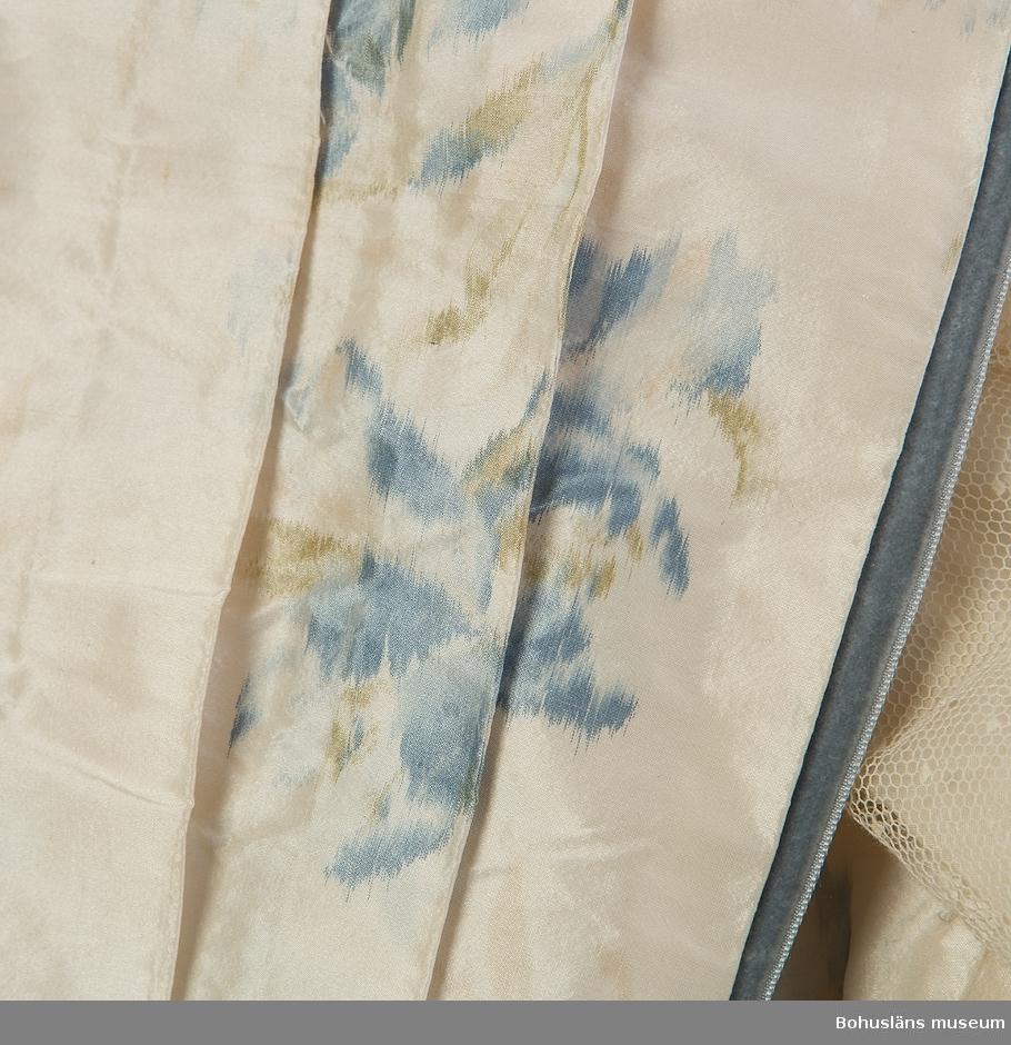 Fram- och ryggstycke av varpmönstrad siden i blått och gulgrönt. Ett ikat-mönster. Motiv: Blombuketter. Del av framstycket lagda veck med tyll över, likaså hög hals av tyll. Stora vida ärmar med bomullssatin. V-formad ringning baktill med en tyllinsättning med bomullssatinfoder. Garneringar av blågrå sammetsband. Från midjan och uppåt 18 cm långa fjädrar insydda. Knäpps med hyskor.