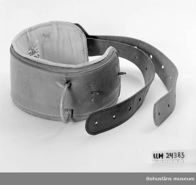 Brett läderbälte med två smalare remmar att spänna åt med. På det breda bältet finns två stycken metallringar. Har använts för att spänna fast oroliga/våldsamma patienter i en säng. Finns både tunnare och kraftigare. Trots bältet kunde patienter sätta sig upp.           Läkartillstånd har krävts innan man använde bälten. Hör ihop med UM024533