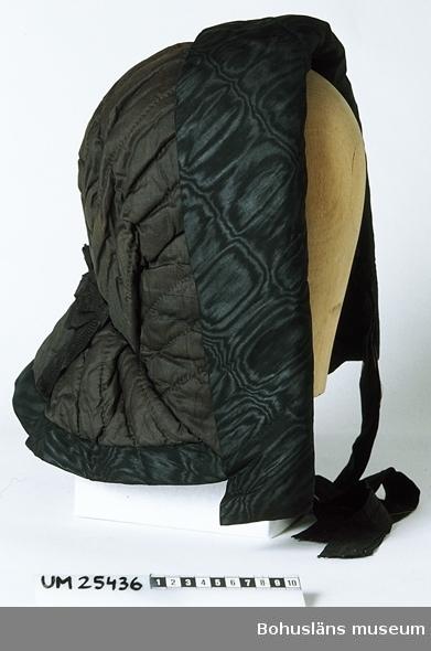 """Matelasserad mössa av svart siden i bahyttliknande modell för kvinna. Mössans framdel är i ett stycke (dock hopskarvad av tre delar). Längs framkanten är en 9,5 cm bred kant av sidenmoaré uppvikt. Framdelen är rynkad mot en volang baktill. Volangen är rundskuren, har ett motveck på vardera sidan om mitt bak och är kantad med en remsa av moaré. I nacken finns en dekor av veckat, ca 5 cm brett, svart sidenband. Mössans foder är längst in ljust gulbrunt linne, längre ut slätt svart siden och ytterst kanten av moaré, ihopskarvad av sju bitar, som mest är synlig på utsidan. Två ca 50 cm långa band att knyta under hakan är fastsydda på insidan. Knappast sliten, endast sidenbanden skadade. Två mycket små hål under den uppvikta kanten fram på vänster sida. Blekt till mörkbrun färg här och var. Mössan har funnits länge i museets samlingar. Okända förvärvsomständigheter. Tillverkningstid osäker. Bedömningen grundar sig på vad litteraturen säger. Där talas om artonhundrafemtiotalets nackvolang, som skulle skydda damernas nackar mot sol. Det står även att bahytternas brätten blev mindre från 1840-talet och att på 1860-talet försvann hattar av bahyttmodell.  Kråka: ur Svenska akademiens ordbok: """"Betydelse: 4)  [jfr motsv. anv. i nor.] (i sht förr) kvinnohatt l. hattliknande kvinnohuvudbonad som baktill omsluter huvudet o. framtill är försedd med (urspr. vidt, ansiktet inramande) brätte (vanl. äv. försedd med hakband). BREMER Dal. 30 (1845). Med empiren kom kråkan i bruk, och den skulle hålla sig genom många förändringar i öfver femtio år. KLEEN Kvinn. 40 (1910). LAGERLÖF Mårb. 34 1922. jfr BARN-KRÅKA.  [KRÅKA II.5]  Litteratur: Kleen, Else, Kvinnor och kläder En krönika om adertonhundratalet Stockholm 1910, sid 123.  Resare, Ann, Klädd i hatt, Trelleborg 1993, sid 21-26."""