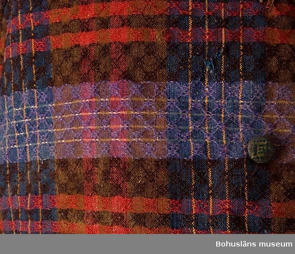 Västens framdel samt kragen vävd i en kypertvariant, gåsögon på 8 skaft. Rutig i rött, brunrött, brunt, blått, lila och orange tunt ullgarn samt ljust gult silkeinslag. Baksida i handspunnen tuskaftsvävd bomull, påsydd slejf. Foder av ljust linnetyg, tuskaft. Västens rutmönstrade framsida samt de tre fickorna kantade med ett fiskbensmönstrat band (av silke/kamgarn och bomull). Ursprungligen 10 klädda knappar, två saknas. Klädda med mönstervävt eller sytt textil av silke i blått och gulgrönt. Senare uttagen/vigdad ca 8 cm genom att falla in ett ljusare brunt bomullstyg och ett kypertvävt linnetyg som foder. Alla sömmar sydda för hand. Bruna fläckar främst på fodret; trasiga sömmar och några revor. Framstyckets färger välbevarade. Garnerna till tyget växtfärgade.