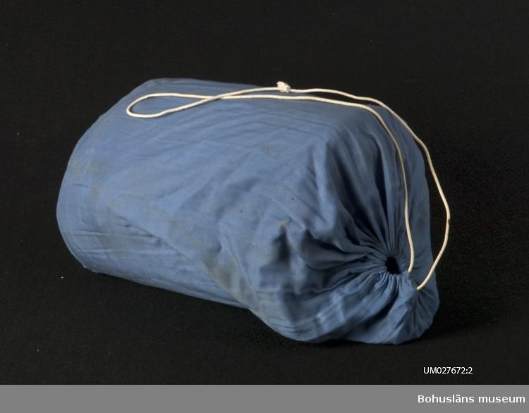 Vadderad sovsäck (UM027672:1) i mellanblått bomullstyg med maskinstickningar i ringlande form. Dragkedja av metall på ovansidan.  Tillhörande tygfodral (UM027672:2) med dragsko och bärhandtag. Solkig; fläckar och hål.  Sovsäcken användes under flera sommarsäsonger i samband med tältning och/eller övernattning hos vänner. Familjemedlemmarna (föräldrar och tre barn) hade användning av den vid olika tillfällen.  Barnen sov i den när de var på 4H-läger, idrottstävlingar med övernattning med mera.   Se exempel på varukataloger i Enskilda Arkiv.  För ytterligare upplysningar om insamlingen av föremål från ABC-Fabrikerna, om utställningen år 2001 samt litteratur, se UM027670:001 - UM027670:006