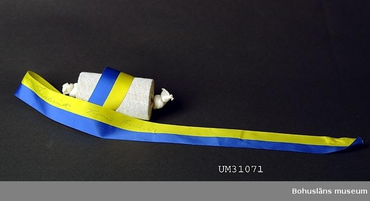 Blågult ripsvävt sidenband med två namntecknngar i bläck, Claes Nabrink och Erland Holmdahl.