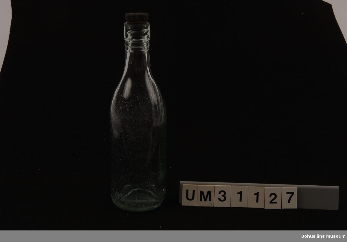 Bryggeriflaska, ca 60 cl., i svagt gröntonat glas med gjutna refflor för skruvkork. Märkt i relief i glasmassan runt flaskans nedre kant: HULL BREWERY CO LTD  Svart bakelitskruvkork med gummi märkt: ROBINSON & SPEIGHT LTD HULL TRADE MARK  Funnen som vrakgods i Bohuslän.  Bernhardson beskriver barnens vrakletning i boken  Bohuslän - från Wämmer ock Kräppe  s. 128: Ätter e hale västa å massa lanfall brogga ongane sprenge langs strännena å röra i tanga - de leda ätter granne bôttlar mä konsti korkar å färger, de sanka på sånna. (Efter hård västanvind och högvatten brukade barnen springa längs stränderna och sparka i tången. Barnen sökte efter vackra buteljer med olikartade skruvkorkar och färger. Man samlade på sådana flaskor). Tidsbild 1920-talet  Litt: Bernhardson, C. G.: Bohuslän - från Wämmer ocH Kräppe. Uddevalla 1985.  För ytterligare upplysningar om förvärvet, se UM31100.