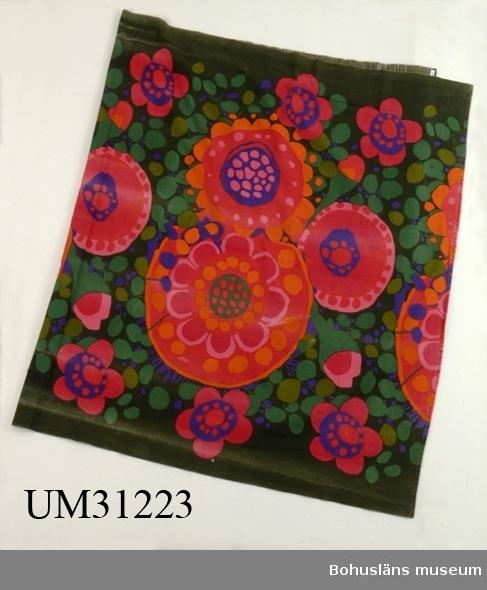 """Funktion: Rumsavskiljare i tångbadhus. Draperi av bomull, tryckt blommigt mönster i grönt, rött, rosa och lila på ripsartat (inslaget)vävt tuskafttyg. Ljusare slitna ränder, enstaka hål. Mönstret heter """"Ekerö"""", och ritades av Saini Salonen runt 1969 till kollektionen """"Linje Hemma"""" för Borås Wäfveri."""