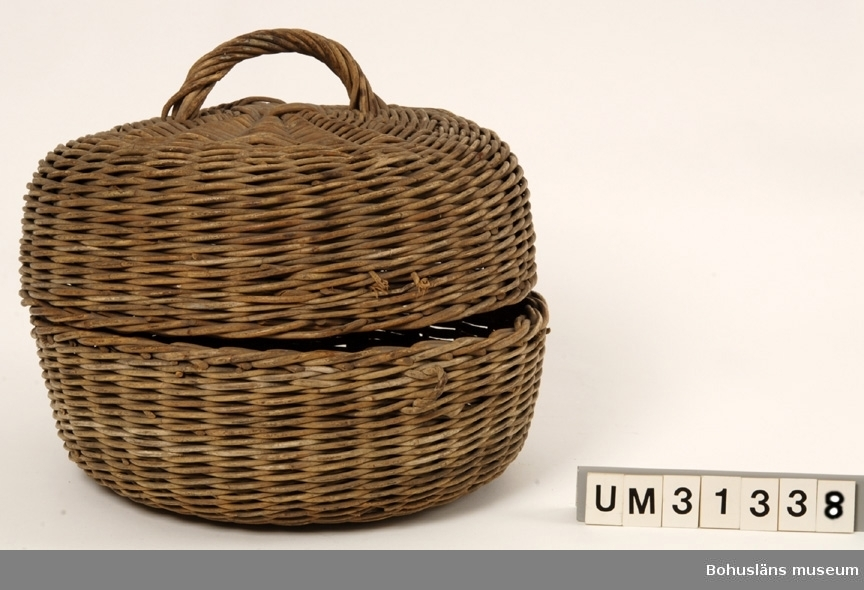 """Föremålet visas i basutställningen Uddevalla genom tiderna, Bohusläns museum, Uddevalla.  Flätad rund korg bestående av två likadana halvor sammansatta  med två flätade """"gångjärn"""" och med  flätade låsanordningar på motsatta sidan, den översta är trasig. På locket ett flätat handtag.  Vid förvärvet var korgen tillstängd med en tunn ståltrådsögla och en bit snöre.  I korgar av denna typ transporterades curlingstenarna ursprungligen.  Korgen  förvarades i Sportstugan vid Bjursjön som BCK byggde tillsammans med några andra föreningar 1933. Här var BCK andelsägare och disponerade ett eget rum.   Korgen ingår i en gåva från Bohuslänska curlingklubben, BCK genom Bengt  Hansson. Klubben har idag inga möjligheter att förvara äldre föreningsmaterial. Sedan 2007 står man utan """"istid"""", träningstid i hallen i Uddevalla efter det att ishockeyn tilldelats denna. Därför kan man inte bedriva någon verksamhet f. n. (2008).  Artikel i Bohusläningen 1998-03-11 """"Äldsta curlingstenen från 1511"""", om curling och curlingstenar. Notis i Populär historia nr 3/2001 """"Stenkul på 1800-talet"""". Artikel i Göteborgs-Posten 2002-02-12 """"Hårdvarufabriken"""". Bohuslänska curlingklubben 1852-2003 (folder beskrivande en  mer än 150-årig verksamhet); Bohuslänska Ck i Uddevalla sedan 1852 (informationsblad 2003). Artikel i Göteborgs-Posten 2006-02-10 """"Tillbaka till curlingens stenålder"""".  Se Bilagepärmen UM31336 för kopia av artikel Bohuslänska Curlingklubben1852 - 2002 av Gunnar Klasson samt UM4661 med artiklar om BCK och om curlingstenar.  Se också arkivmaterial och föremål från BCK som  skänktes till Uddevalla museum 1950 respektive 1975  och som förvaras i Bohusläns Föreningsarkiv; UM5352, UM75.3.1 - UM75.3.2, UM75.3.5 - UM75.3.6 och enligt katalogen överförts dit 16/11 2000.  Litt: Bohus-Posten 1947. Artikel om Bohuslänska Curlingklubben.  Olsson, Hugo: Uddevalla, en bildbok,  Bohusläns museums förlag. Uddevalla 1983, s. 158. Bohuslänska Curlingklubben. Artikel i Släktkrönikan. Tidning för medlemmar av Sl"""