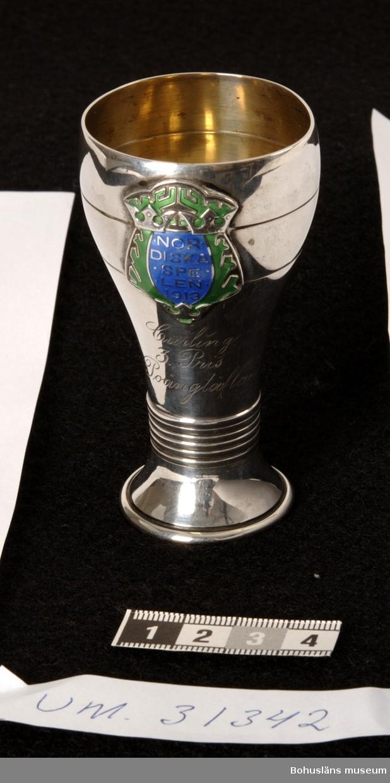 """Pokal av silver i form av en pokal, den kupade delen något insvängd. Cuppan dekorerad med två ingraverade linjer och runt den koniska foten dekore av  pressade upphöjda linjeband. På cuppan sitter fästat ett sköldformat märke med blå och grön emalj och texten: NORDISKA SPELEN 1913 Därunder ingraverade texten: Curling  3. Pris  Poängtäflan  På fotens utsida fyra stämplar: CG HALLBERG, kattfot, Stockholms stads stämpel  samt  årsbokstav L7 (=1913)  Silverföremålen UM31341- UM31344 skänktes till BCK i mars 2008 av Violet Thorburn, dotter till David Thorburn, Uddevalla. Alban E. Thorburn (1862-1933), far till David Thorburn (1894-1974) är troligen den som haft omhand prispokalen.  Konsul Alban E. Thorburn var en av Bohuslänska Curlingklubbens presidenter. """"Bland de mest verksamma krafterna inom klubben torde i främsta rummet böra nämnas konsul Alban E. Thorburn. I flera årtionden offrade han tid och krafter för klubben. Han representerade den i Stockholm och ledde i början av 20-talet en glansrik turné i Skottland."""" Bohus-Posten 1947,  ur Släktkrönikan 1966 , se nedan.  Se Bilagepärmen UM31336 för kopia av artikel Bohuslänska Curlingklubben1852 - 2002 av Gunnar Klasson samt UM4661 med artiklar om BCK och om curlingstenar.  Se också arkivmaterial och föremål från BCK som skänktes till Uddevalla museum 1950 respektive 1975 och som förvaras i Bohusläns Föreningsarkiv; UM5352, UM75.3.1 - UM75.3.2, UM75.3.5 - UM75.3.6 och enligt katalogen överförts dit 16/11 2000.  Litt: Bohus-Posten 1947. Artikel om Bohuslänska Curlingklubben.  Olsson, Hugo: Uddevalla, en bildbok,  Bohusläns museums förlag. Uddevalla 1983, s. 158. Bohuslänska Curlingklubben. Artikel i Släktkrönikan. Tidning för medlemmar av Släktföreningen Thorburn-Macfie. Nr. 30 1966, s. 20-21."""
