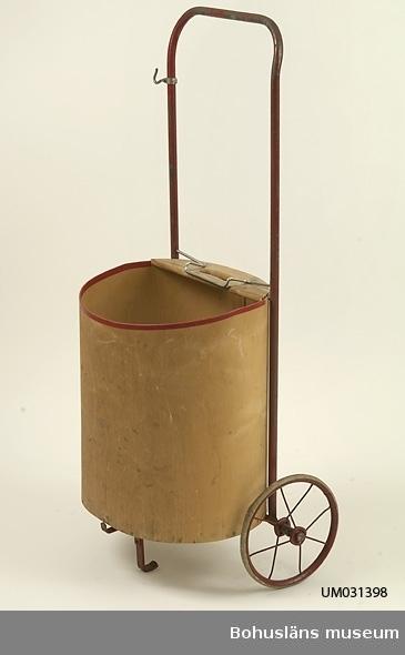 """Shoppingvagn med löstagbar väskdel av plywood, 1940-50-tal. Vagnen stod alltid på sin bestämda plats i köket. Vagnen användes in på 1970-talet och så länge som det fanns affär i Sundsandvik. Man gick ner via Bagarbacken, en grusväg som ledde ner till färjeläget. I Sundsandvik fanns två mataffärer, """"Marcussons Livs"""" och ytterligare en butik vid färjeläget. Ett bageri låg vid färjeläget som bakade jättegott bröd. Här ringlade sig köerna långa på lördagarna när passagerarna väntade på färjan. På 1950-talet hette affären """"Sandstedts Livs"""". Mjölk hämtades i mjölkkruka av aluminium i en av """"De tre Sundsgårdarna"""", hos Arvid Jacobsson i närmsta gården. De vuxna tyckte att mjölken med sin feta grädde var så god, men det tyckte inte barnen. Dessutom luktade det illa i ladugården, tyckte barnen. Arvid Jacobson var också den som sålde tomten som sommarstugan byggdes på.  Föremålet har använts av familjen Abrahamson i deras sommarstuga i Sundsandvik, byggd 1939. För ytterligare upplysningar om förvärvet, se UM031385."""