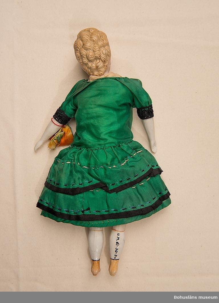 Docka med huvud och armar av ofärgad biskvi. Troligtvis av tyskt ursprung omkring 1870. Blont hår uppsatt och med ett markerat hårspänne i svart gjutet direkt på huvudet. Hål i öronen men örhängen saknas. Anletsdragen är målade och hela huvuddelen är svagt rosamålad till skillnad från armar och ben vilka är vita. Huvuddelen är fastsydd i tygkroppen med två hål i fram och bak. Underbenen är av biskvi med röda strumpeband målade under knäna. Benen är formade som stövlar med hög klack vilka är brunmålade med  svart kant. Klänning av grönt sidentyg med två volanger. Svart spets på hela framstyckets mittparti och volangerna har svarta fållar som sticker fram. Halvlång ärm med svart spets i kanten. Underklänning i linne med mycket spets i livet vilket syns igenom under klänningens svarta spetsliv. Mamelucker helt i spets. Kring sin vänstra arm har hon en ridicule UM61.03.003B i gul/orange/grönfärgat siden.  Litteratur: Goodfellow, Caroline: Dockboken. Allt om dockor. Forum bokförlag 1994.  Ur punktnummerkatalogen 1958-1976: Frk. Ida Svanberg, Uddevalla.