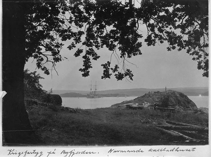 """Text på kort: """"Krigsfartyg på Byfjorden. Nuvarande kallbadhuset å Gustafsberg ligger på klippan med trävirket""""."""