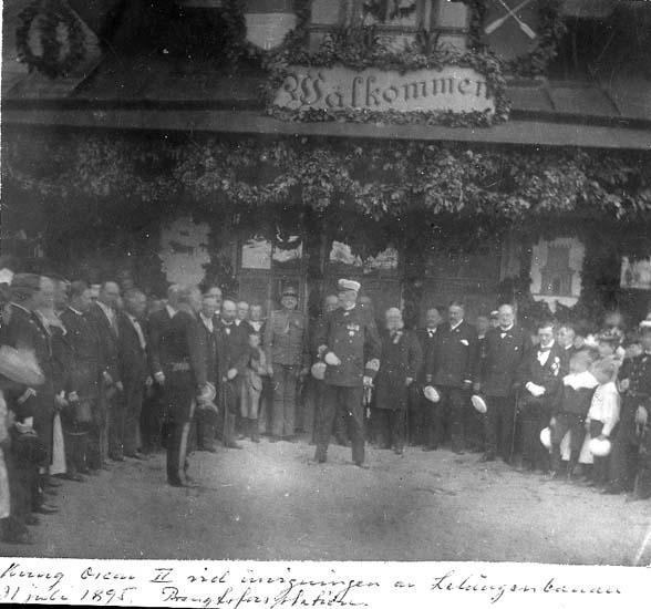 """Text på kortet: """"Kung Oscar II vid invigningen av Lelångenbanan 31 juli 1895. Bengtsforsstationen""""."""
