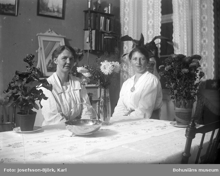 Två damer bland blommor i ett rum