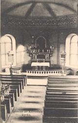 """Tryckt text på kortet: """"Interiör av Klövedals kyrka""""."""