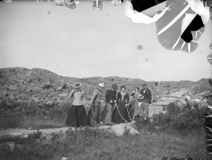 """Enligt text som medföljde bilden: """"Lysekil. Vid Pinnevik. Herr Eric Carlsson, fröknarna Tora och Ruth Carlsson, Ellen och Anna Lindberg o. K. Lundgren m.fl. 26/7 1899."""""""