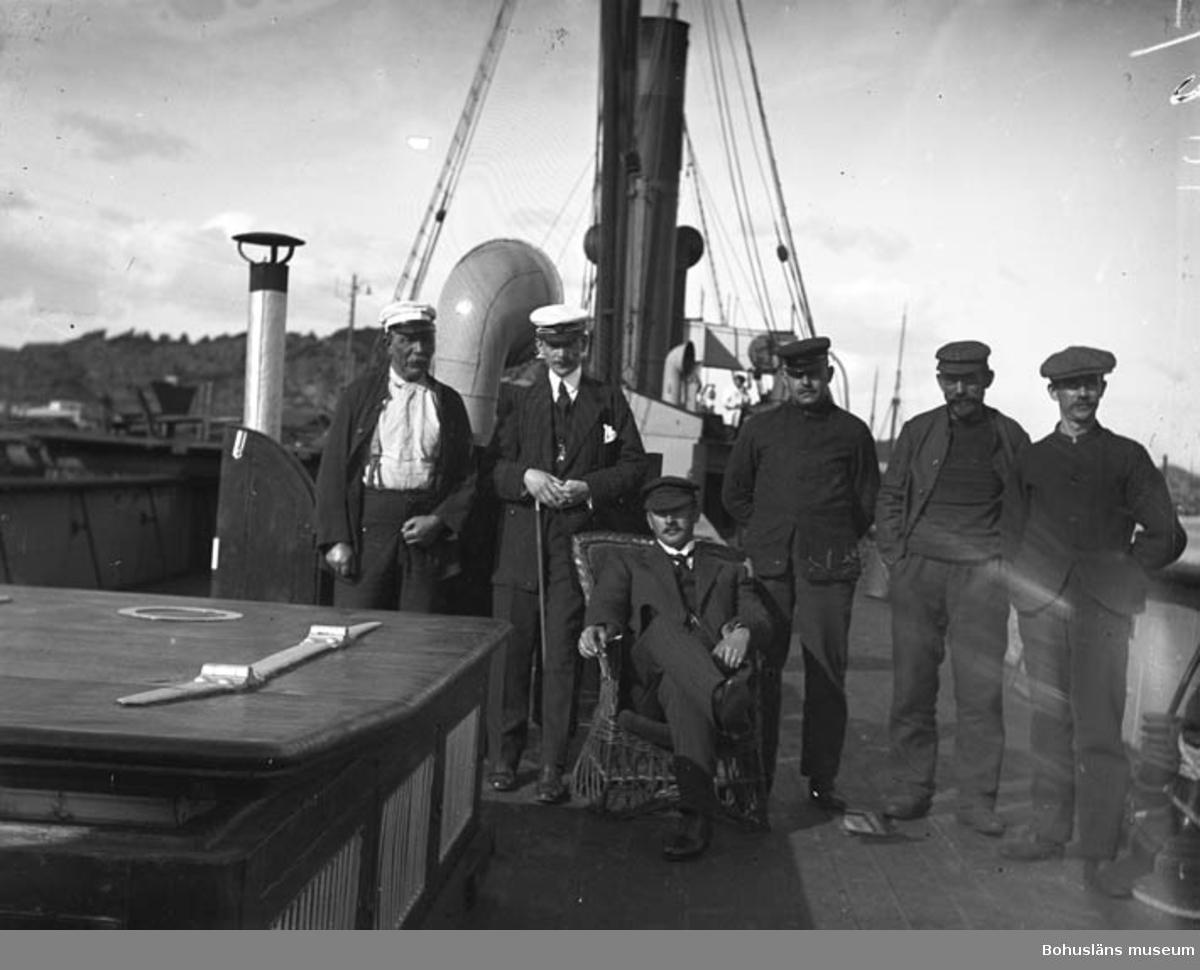 """Text till bilden: """"Däckbild på Ångaren. Två från vänster S. P. Pettersson. I stolen ev kapten Thorburn""""."""