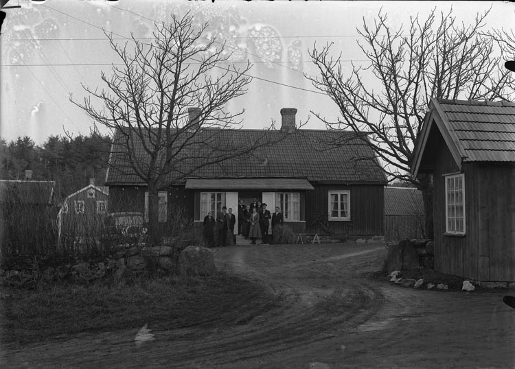 """Enligt fotografens anteckningar: """"1932, 111. Faleby, den gamla byggnaden numer riven, numera en ny. Lantbrukare Fritz Östlund Faleby, hustrun Ida Blomdal Torsby Bohuslän""""."""