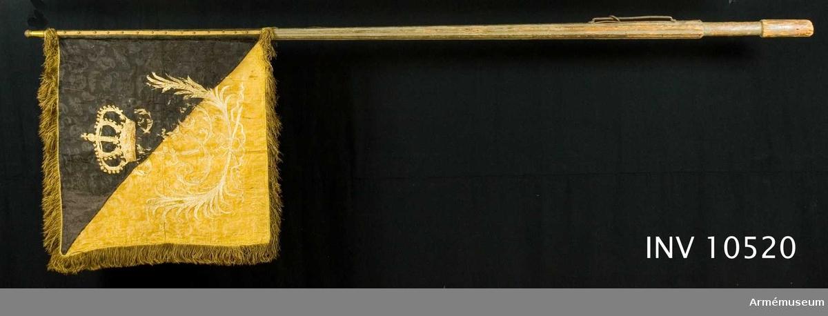 Grupp B. Duk av dubbel damast, diagonalt delad i två fält. Det övre, inre  svart - det nedre, yttre gult och därpå broderat. På inre sidan  ett upprättstående lejon i påsydd atlas, gult å det svarta,  svart å det gula med modellering i silke. På den svarta delen  två stjärnor i gult silke, den ena framför, den andra bakom  lejonet. På yttre sidan, i plattsöm, med vitt silke dubbelt F  krönt av rödfodrad, sluten krona. I båge därunder tvenne korsade  hopknutna palmkvistar, runt kanten frans av guldsilke 70 mm  bred, fäst vid stången med tre gula sidenband och mässings- spikar. MÅTT: Total l:2610 mm, till greppet 210 mm.  Greppet 210 mm, till duken 1490 mm. Diameter upptill 33 mm,  nedom duken 430 mm, ovan greppet 60 mm och i greppet 50 mm. Holk 100 mm hög. Tillverkad av Johan Wijkman år 1720. -------------------------------------1976. Sidenets damast med ett sammanhängande mönster.  Efter år 1700.